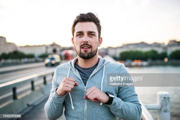 young sporty man standing in a boxing position on the bridge outside in a city. - hoodie headphones stock pictures, royalty-free photos & images