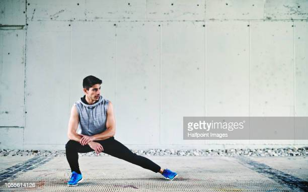 Young sporty man stretching legs outdoors in the city. Copy space.