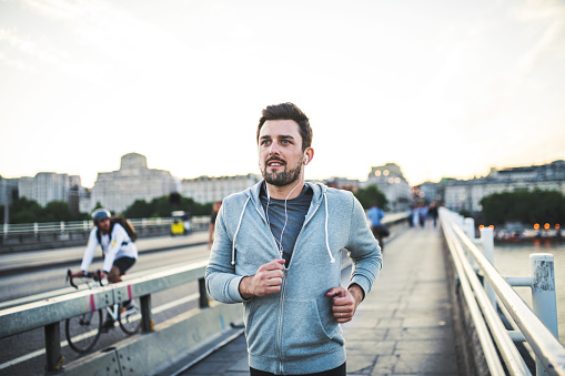 Young sporty man with earphones running on the bridge outside in a city. - gettyimageskorea
