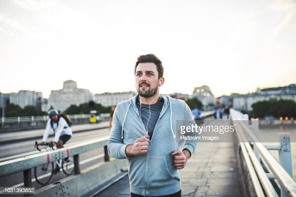 young sporty man with earphones running on the bridge outside in a city. - rennen stockfoto's en -beelden