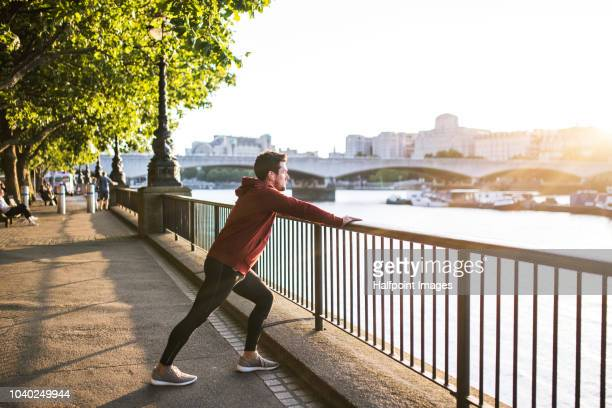 young sporty man with earphones stretching on a railing outside in a london city. - dehnen stock-fotos und bilder