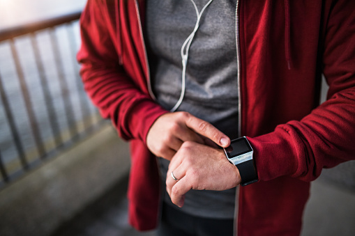 Young sporty man with earphones using smart watch outside in a city. - gettyimageskorea