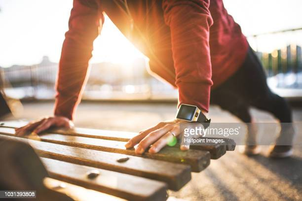 young sporty man with smart watch doing push-ups on a bench outside in a city at sunset. - push ups stock pictures, royalty-free photos & images