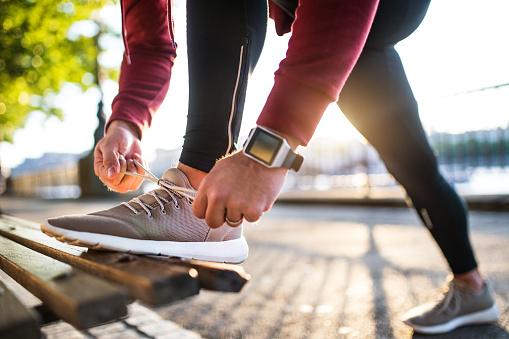 Young sporty man with smart watch tying shoelaces on a bench outside in a city at sunset. - gettyimageskorea