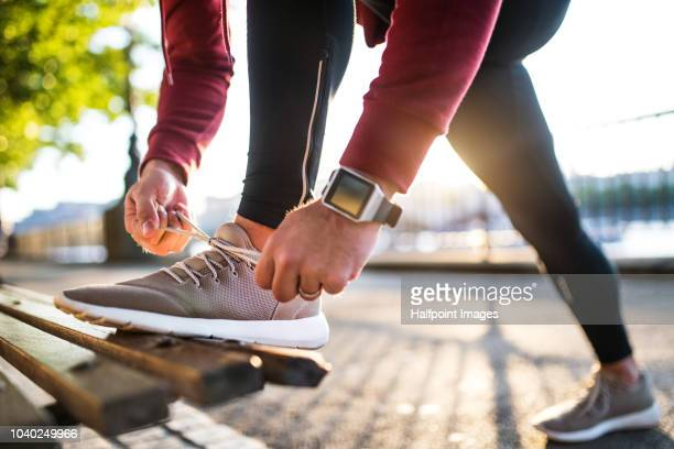 young sporty man with smart watch tying shoelaces on a bench outside in a city at sunset. - competition stock pictures, royalty-free photos & images