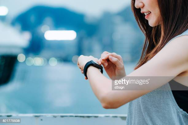Young sporty woman checking her smart watch in city