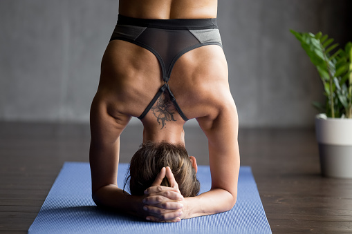 Young sporty woman doing headstand exercise, close up 1036550526