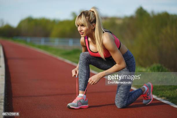 Young sporty woman fixing her shoelaces on running track.