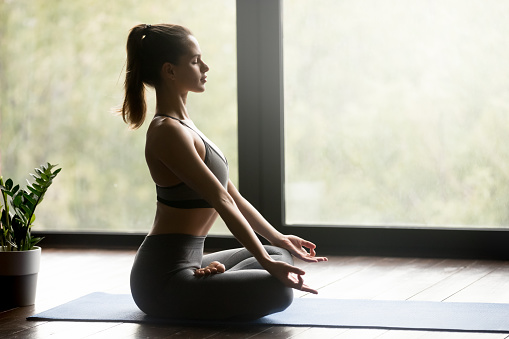 Young sporty woman in Half Lotus pose, side view 1036550412