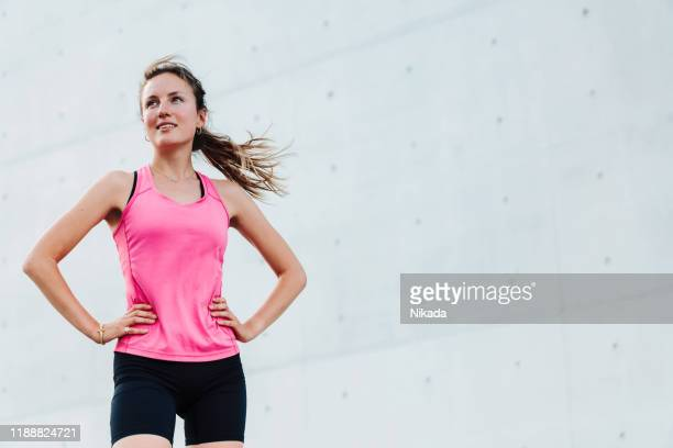 young sporty woman in modern business district - athletics stock pictures, royalty-free photos & images