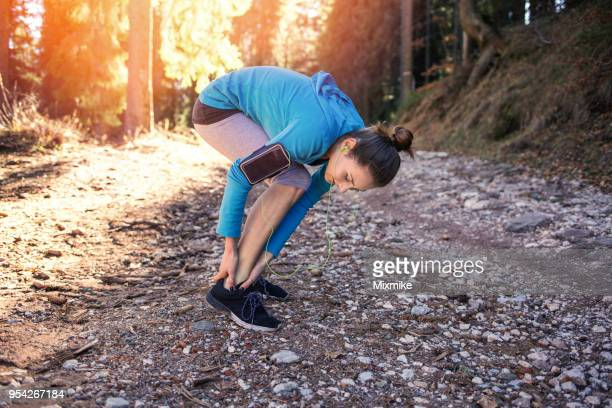 young sporty woman massaging her ankle - sprain stock pictures, royalty-free photos & images