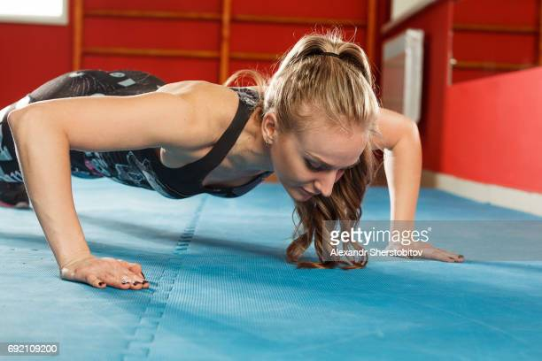 young sporty woman performing push-ups