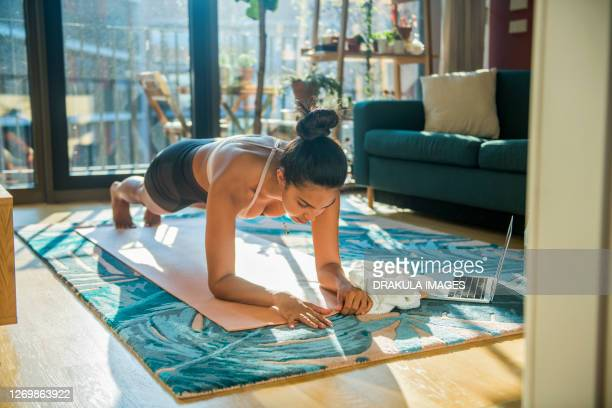 young sporty woman practicing at home - plank position stock pictures, royalty-free photos & images
