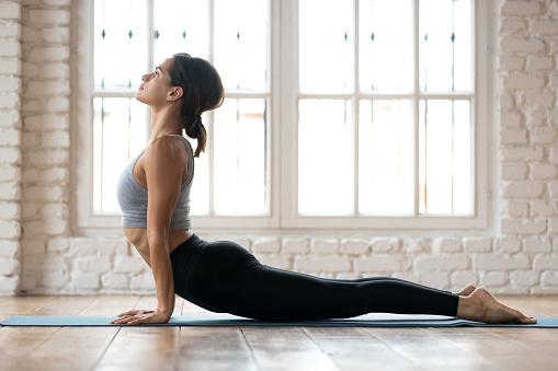 Young sporty woman practicing yoga, doing upward facing dog exercise 1076946698