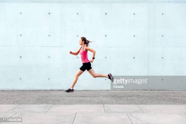 junge sportliche frau läuft vor betonwand - joggen stock-fotos und bilder
