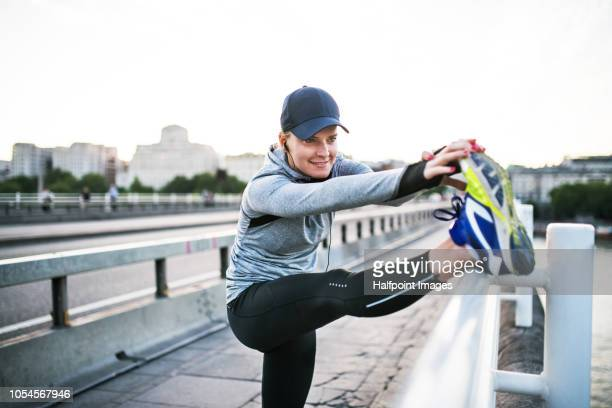 Young sporty woman stretching legs on the bridge outside in a city.