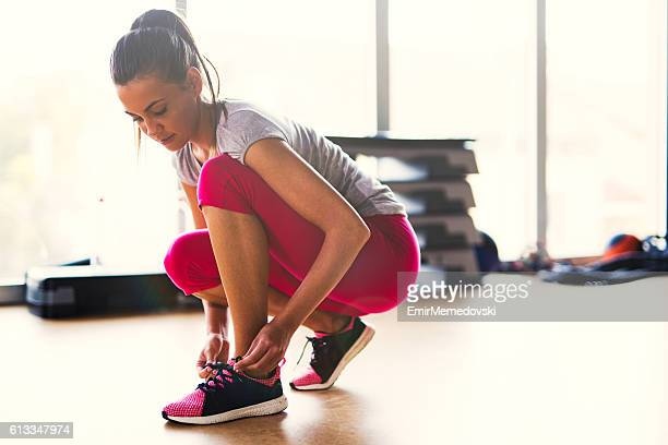 young sporty woman tying shoelaces  at the gym. - frau gefesselt stock-fotos und bilder
