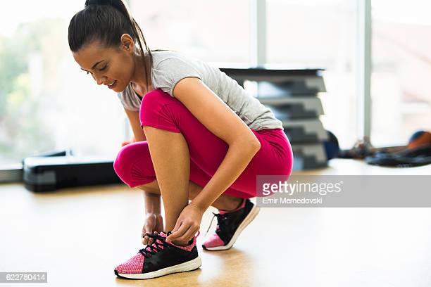 young sporty woman tying shoelaces  at the gym. - binden stock-fotos und bilder