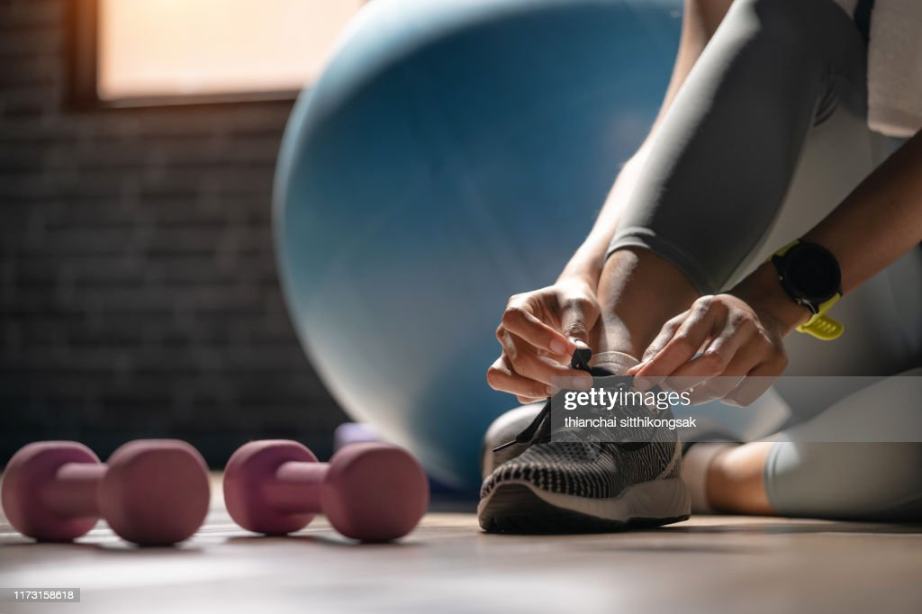 Young sporty woman with smart watch tying shoelaces in fitness : Stock Photo