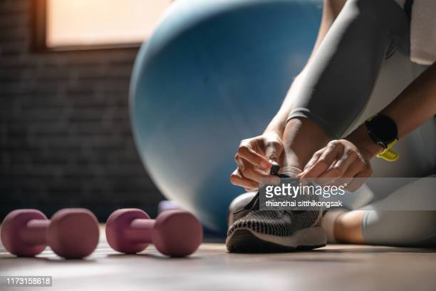 young sporty woman with smart watch tying shoelaces in fitness - motion bildbanksfoton och bilder