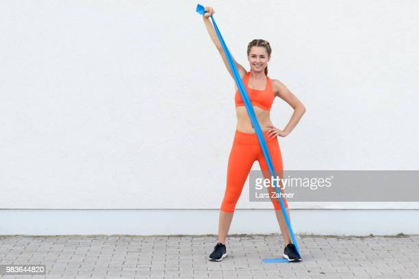 young sporty woman working out with latex bands - women's field event stock pictures, royalty-free photos & images
