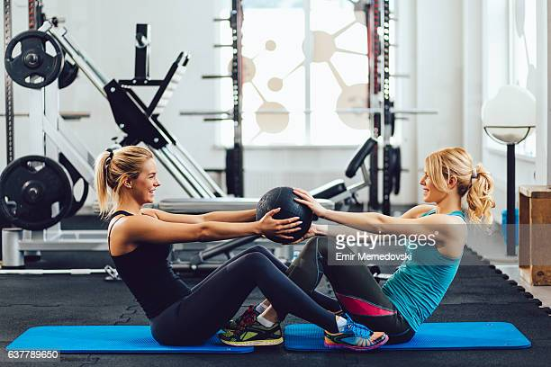 Young sporty women doing doing sit-ups with medicine ball.