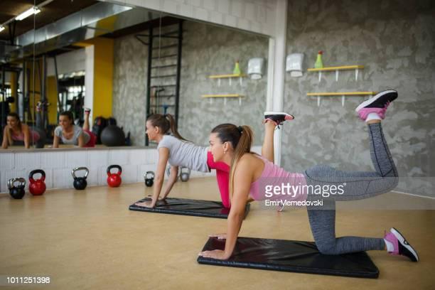jeunes femmes sportives, faire des exercices de jambes et les fesses - culs photos et images de collection