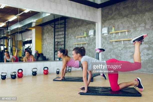 young sporty women doing leg and buttocks exercises - human leg stock pictures, royalty-free photos & images