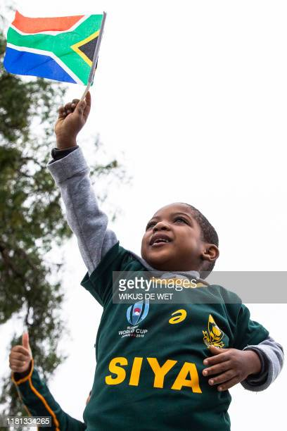 A young Springboks supporter wearing a jersey with the South African Rugby captain Siya Kolisi's name written on waves a South African national flag...