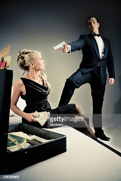 Young Spy Man Holding Gun to Woman Looking Through Suitcase
