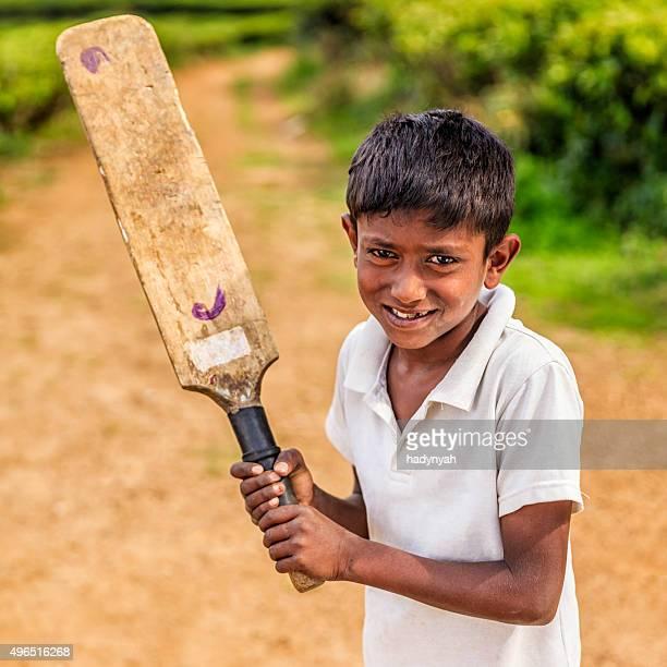 Young Sri Lankan boy playing cricket on tea plantation