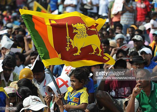 A young Sri Lankan cricket fan holds up the national flag as they watch on a giant screen the Cricket World Cup final match between Sri Lanka and...
