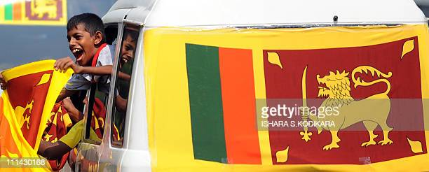 A young Sri Lankan cricket fan waves a Sri Lankan national flag in support of the Sri Lankan cricket team playing against India in the final match of...