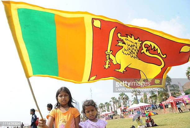 Young Sri Lankan cricket fans hold up the national flag during the Cricket World Cup final match between Sri Lanka and India in Colombo on April 2...
