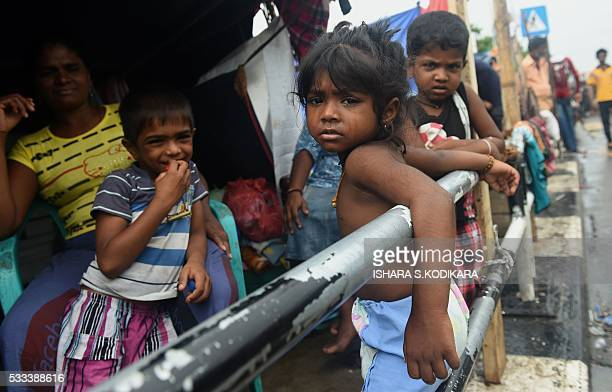 A young Sri Lankan flood victim look on at a roadside camp in Kelaniya on the outskirts of Colombo on May 22 2016 Sri Lankan soldiers pulled more...