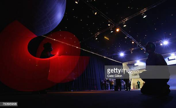 A young Star Wars fan dressed as Darth Vader demonstrates the power of his light saber for his father at the Celebration Europe Exhibition in Excel...