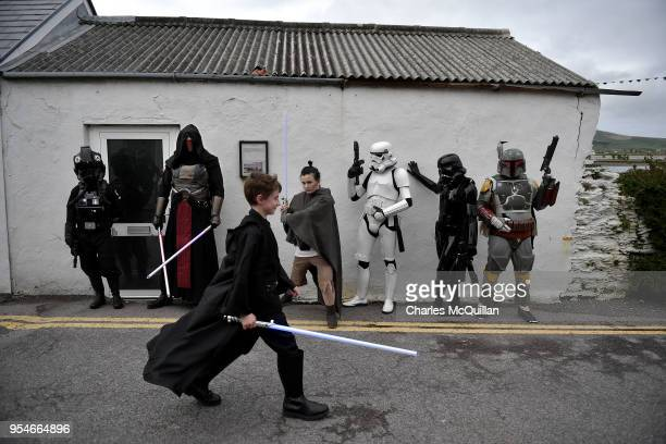 A young Star Wars fan walks past the 501st Irish Legion costume players dressed as Star Wars characters in Portmagee Harbour on International Star...