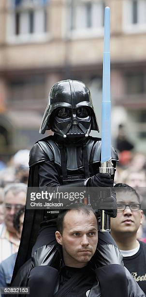 Young Stars Wars fan dressed up as Darth Vader sits on his fathers shoulders as they watch the Royal Philharmonic Orchestra performing the score to...