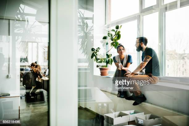 young start up business people sitting in a window and talking - women in see through shirts stock photos and pictures
