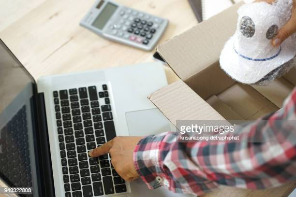 young start up small business owner packing camera cctv in the box at workplace. freelance man seller prepare product for packaging process at home. Online selling, internet marketing, e-commerce concept.