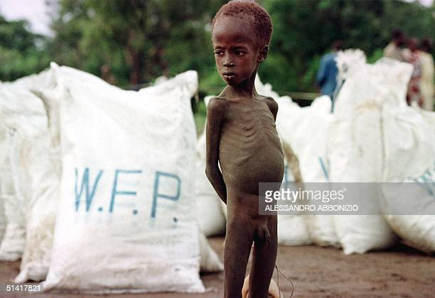 A young starving boy stands in front of relief food bags delivered by the World Food Programme 09 August after an airdrop by the WFP in the village...