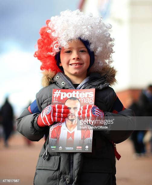 A young Stoke fan wearing a wig proudly holds up his matchday programme before the Barclays Premier League match between Stoke City and Arsenal at...