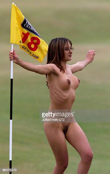 A young streaker invades the 18th green and holds the flag just before the arrival of Tiger Woods of the US onto the green of the Old Course at St...