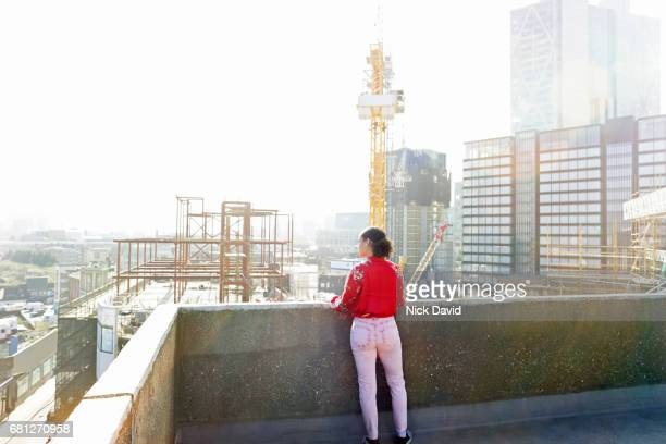 Young street dancer on London rooftop overlooking the city