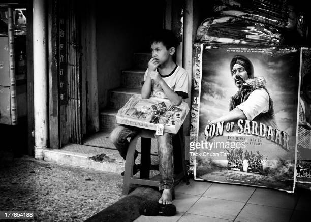 Young street vendor selling various items to passerby with a rather worried look on his face.