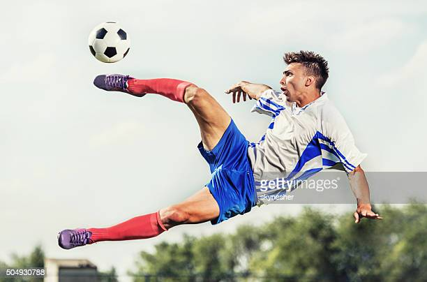 Young striker taking football shot while being in mid air.