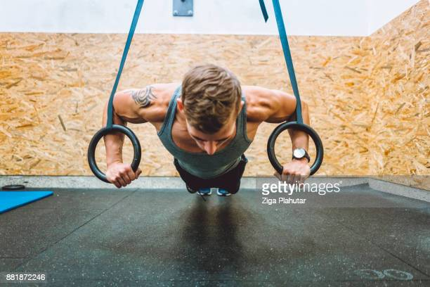 Young strong man practising pull ups with gymnastic rings