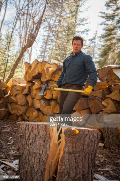 young strong man prepping to swing an axe to chop wood - コロラド州 ニューキャッスル ストックフォトと画像