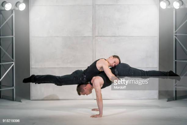 young strong men doing power exercises - black shirt stock pictures, royalty-free photos & images