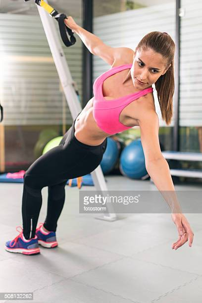 Young strong woman exercising in gym